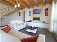 Modernly decorated living area with LED TV, fireplace, DVD player and leather sofas